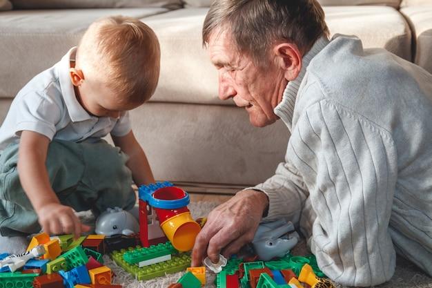 Älterer großvater spielt mit seinem kleinen enkel
