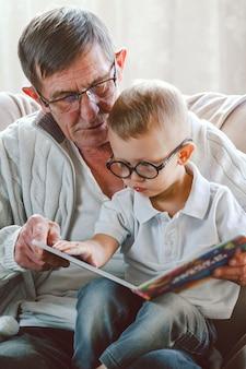Älterer großvater und kleiner enkel lesen zusammen ein buch