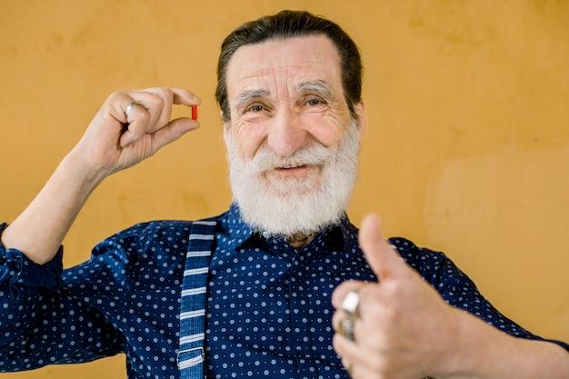 Älterer gutaussehender bärtiger mann, der stilvolle kleidung trägt, gegen gelben hintergrund aufwirft, rote pille in einer hand hält und seinen daumen oben zeigt. älteres alter und medizinkonzept