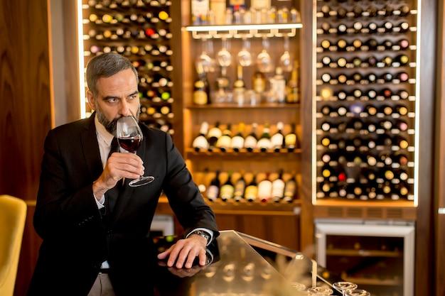 Älterer gutaussehender mann, der rotwein trinkt
