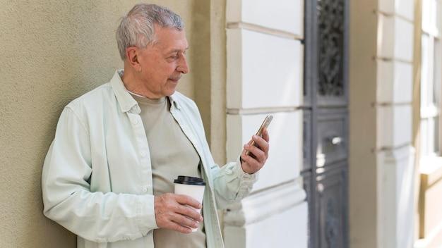 Älterer hält kaffeetasse mittlerer schuss