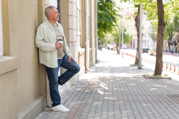 Älterer hält kaffeetasse voll erschossen