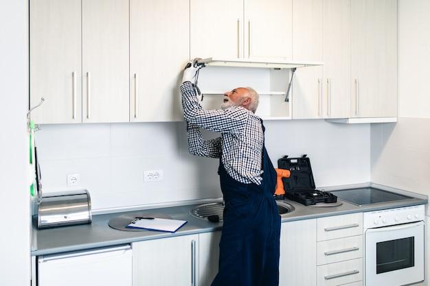 Älterer heimwerker, der in der küche arbeitet. renovierung.