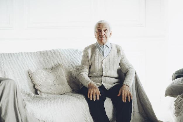 Älterer herr, der auf modernem sofa sitzt und kamera betrachtet