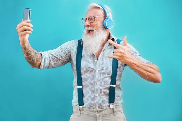 Älterer hippie-mann, der smartphone-app für die schaffung der wiedergabeliste mit rockmusik verwendet
