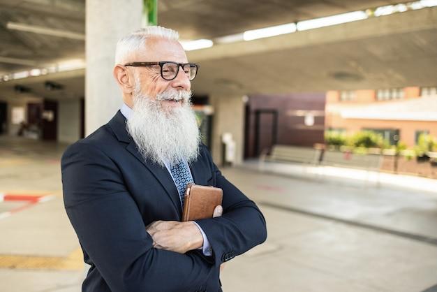 Älterer hipster-geschäftsmann, der am busbahnhof wartet - fokus auf gesicht