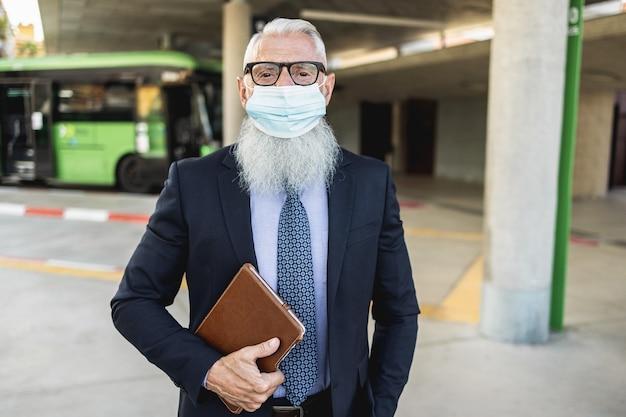 Älterer hipster-mann, der am busbahnhof während des ausbruchs des coronavirus wartet - fokus auf gesicht