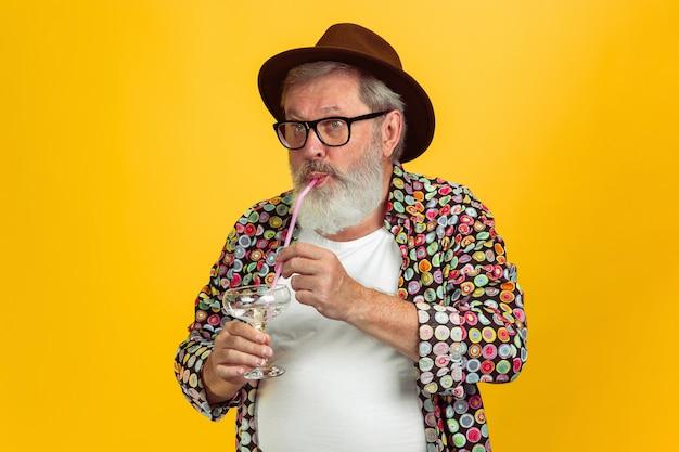 Älterer hipster-mann mit brille posiert auf gelbem hintergrund