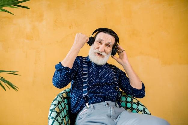 Älterer hübscher bärtiger mann, der stilvolle kleidung trägt, die auf dem stuhl nahe gelber wand mit palme sitzt