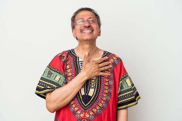 Älterer indischer mann, der ein indisches kostüm einzeln auf weißem hintergrund trägt, lacht laut und hält die hand auf der brust.