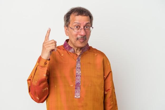 Älterer indischer mann, der ein indisches kostüm einzeln auf weißem hintergrund trägt und eine großartige idee hat, konzept der kreativität.