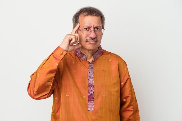 Älterer indischer mann, der ein indisches kostüm einzeln auf weißem hintergrund trägt und mit dem finger auf den tempel zeigt, denkt, konzentriert sich auf eine aufgabe.