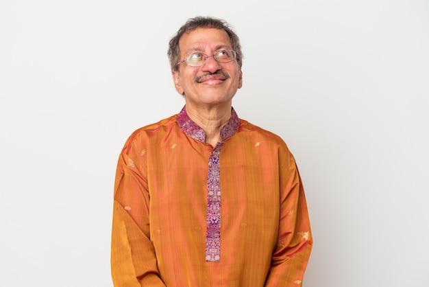 Älterer indischer mann, der ein indisches kostüm trägt, das auf weißem hintergrund isoliert ist und davon träumt, ziele und zwecke zu erreichen