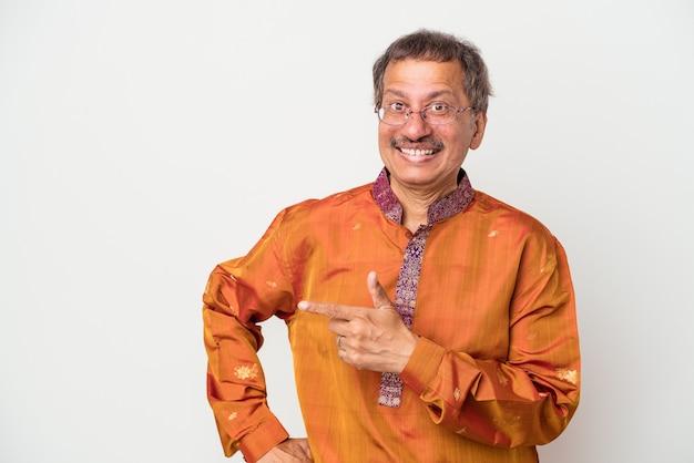 Älterer indischer mann, der ein indisches kostüm trägt, das auf weißem hintergrund lokalisiert wird, lächelt und zeigt beiseite und zeigt etwas an der leerstelle.