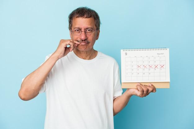 Älterer indischer mann, der einen kalender auf blauem hintergrund mit fingern auf den lippen hält, die ein geheimnis halten.