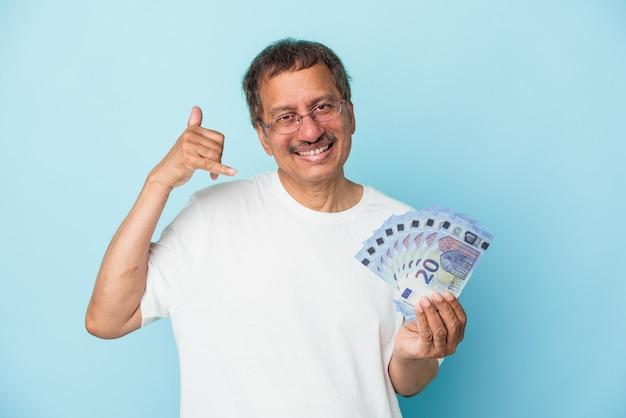 Älterer indischer mann, der rechnung lokalisiert auf blauem hintergrund hält, der eine handyanrufgeste mit den fingern zeigt.