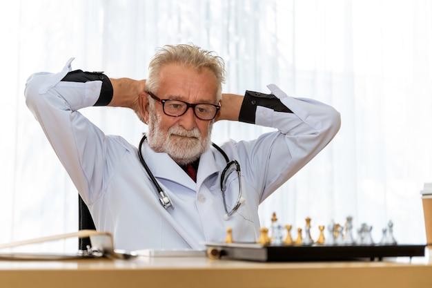 Älterer kaukasischer ernsthafter mannarztkopfschmerz, der ruht und schach im raum spielt.