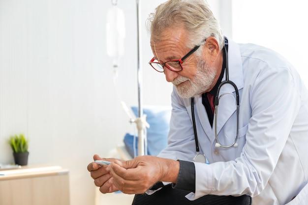 Älterer kaukasischer facharzt, der mit thermometer zur fieberbekämpfung in einer infektion im krankenzimmer hält.