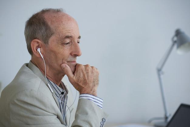 Älterer kaukasischer geschäftsmann, der im büro mit kopfhörern sitzt und laptop betrachtet