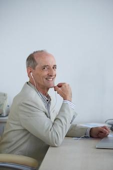 Älterer kaukasischer geschäftsmann mit den kopfhörern, die im büro sitzen