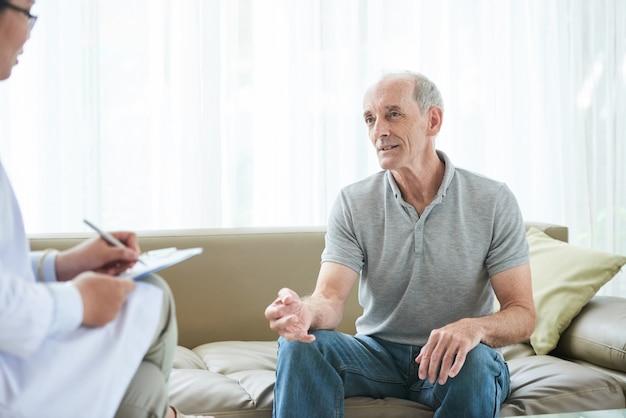 Älterer kaukasischer männlicher patient, der zu hause gesundheitsbeschwerden mit doktor teilt