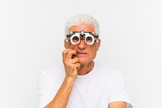 Älterer kaukasischer mann, der beißende fingernägel eines optometrikerversuchsrahmens, nervös und sehr besorgt trägt.