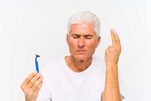 Älterer kaukasischer mann, der eine rasierklinge lokalisierte kreuzende finger für das haben des glücks hält