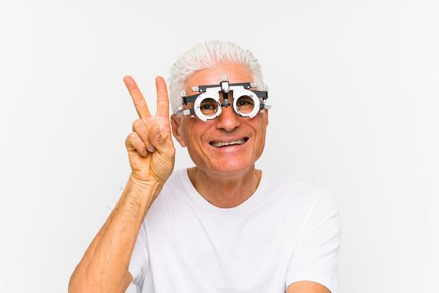 Älterer kaukasischer mann, der einen optiker-versuchsrahmen trägt, der siegeszeichen zeigt und breit lächelt.