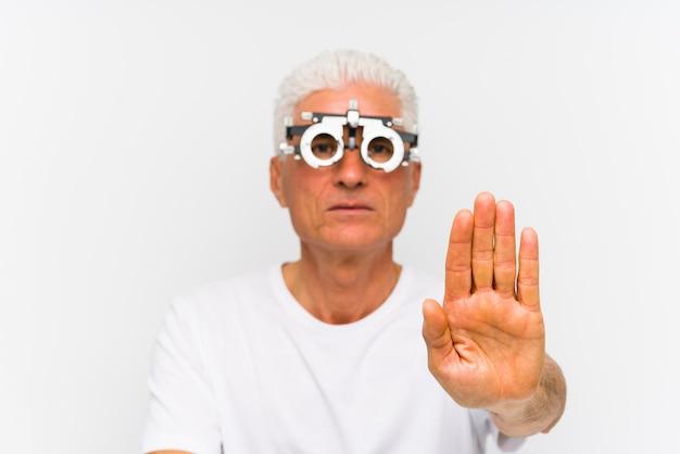 Älterer kaukasischer mann, der einen optometrikerversuchsrahmen steht mit der ausgestreckten hand zeigt das stoppschild und verhindert sie trägt.