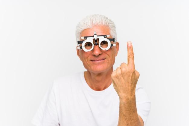 Älterer kaukasischer mann, der einen optometrikerversuchsrahmen zeigt nummer eins mit dem finger trägt.