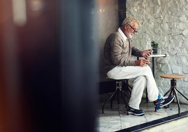 Älterer kaukasischer mann, der handy an café ourdoors verwendet