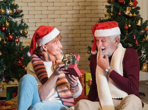 Älterer kaukasischer mann in weihnachtsmütze fühlt sich glücklich und überrascht mit weihnachtsgeschenk von seiner frau. paar feiert weihnachten und neujahr zu hause. romantischer urlaub.