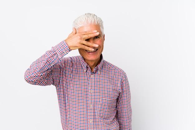 Älterer kaukasischer mann lokalisiertes blinken durch finger, verlegenes bedeckungsgesicht.