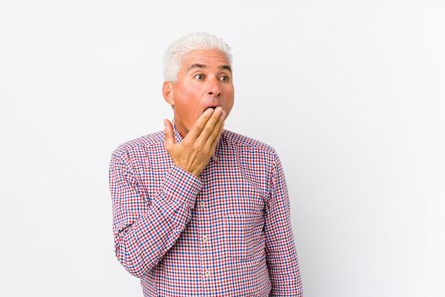 Älterer kaukasischer mann lokalisiertes gähnen, einen müden gestenbedeckungsmund mit der hand zeigend.