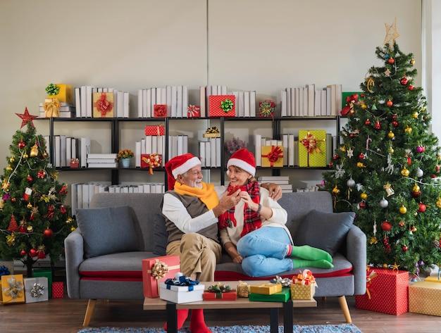Älterer kaukasischer mann mit weihnachtsmann-hut, der seinem breiten paar ein weihnachtsgeschenk gibt, während er auf der sofacouch mit geschmücktem weihnachtsbaum im wohnzimmer zu hause sitzt. glückliches überraschungsgeschenk vom ehemann.