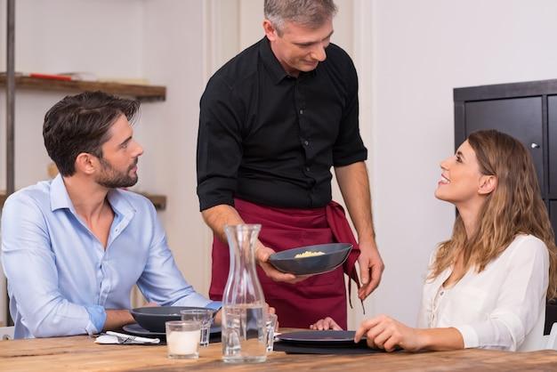 Älterer kellner, der einem jungen glücklichen paar in einem restaurant essen serviert. chefkoch serviert seine spezialität küche für junge paare. glücklicher zufriedener koch, der der jungen frau essen serviert.