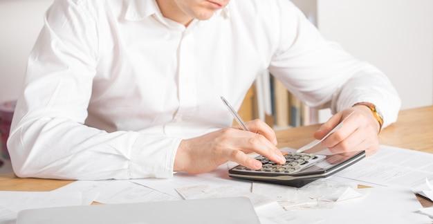 Älterer kleinunternehmer, der die finanzabrechnungen berechnet - unternehmer, der mit laptop und taschenrechner arbeitet und die finanziellen ausgaben für die gründung eines neuen unternehmens berechnet und analysiert