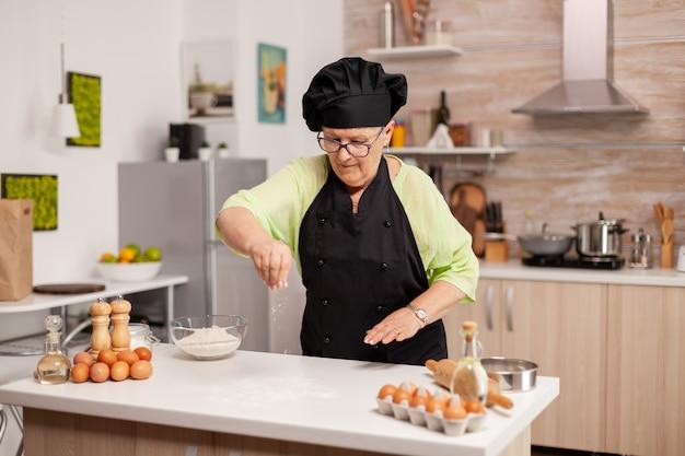 Älterer koch mit einheitlichem bestreuen von mehl in der heimischen küche mit schürze und bonette