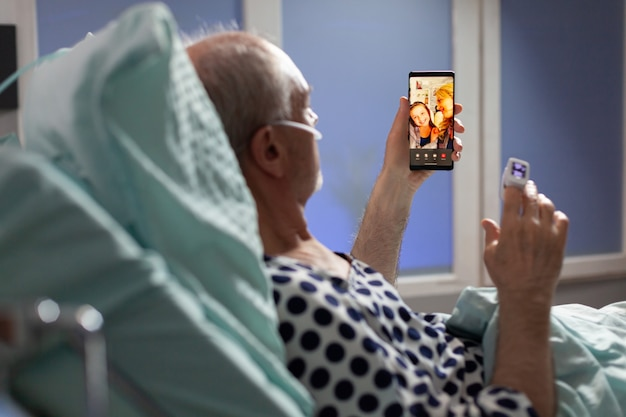 Älterer kranker mann, der durch sauerstoffschlauch atmet und verwandten begrüßt, im krankenhausbett liegt und telefone hält, über die genesung diskutiert