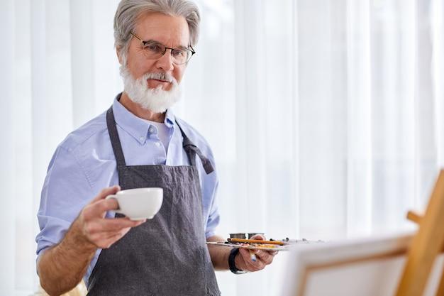 Älterer künstler mann trinken tee während der arbeit im studio, grauhaariger mann in der schürze genießt den prozess des zeichnens