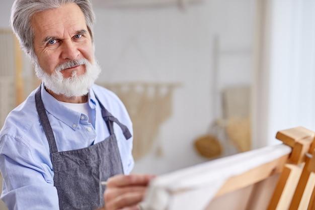 Älterer künstlermann mit falten, die camea während der arbeit auf leinwand, im kunststudio betrachten