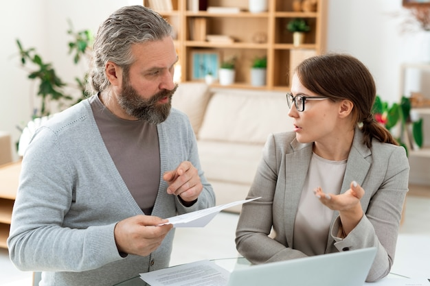 Älterer kunde mit papier, in dem einzelheiten der vertragsbedingungen angegeben sind, während er sich bei der sitzung mit dem finanzberater oder wirtschaftsprüfer berät