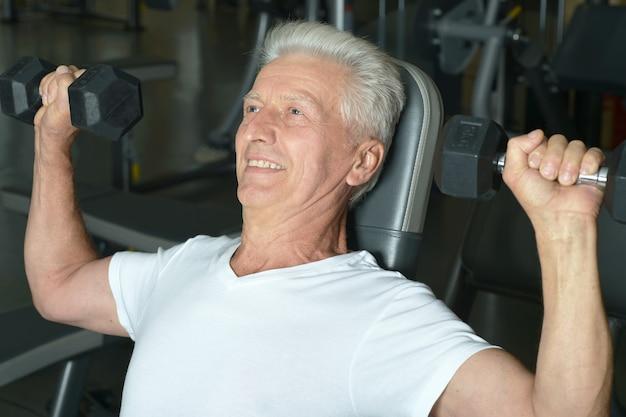 Älterer lächelnder mann in einem fitnessstudio, das trainiert