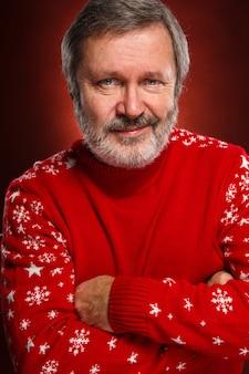 Älterer lächelnder mann in einem roten weihnachtspullover