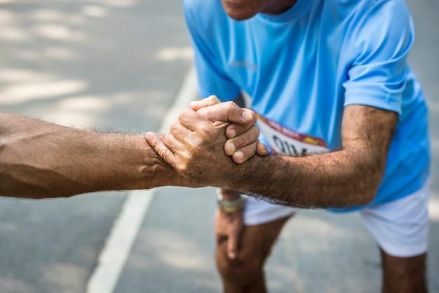 Älterer läufer, der eine helfende hand gibt