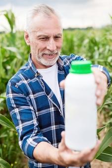 Älterer landwirt, der auf einem gebiet schaut auf einer flasche mit mineraldüngern steht.