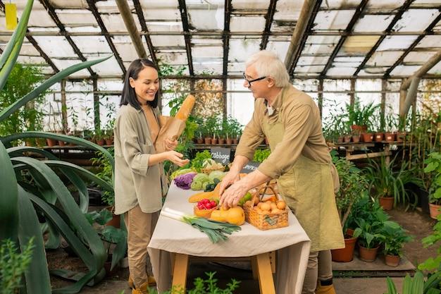 Älterer landwirt in der schürze, der mit verschiedenen produkten am tisch steht und asiatischen kunden bio-lebensmittel anbietet
