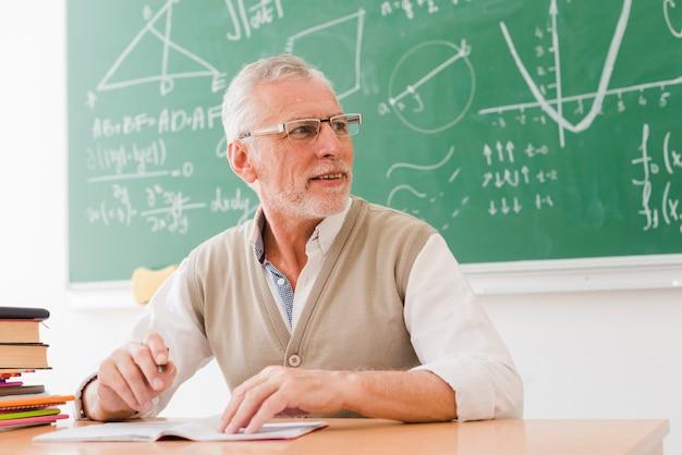 Älterer lehrer, der am schreibtisch im klassenzimmer sitzt