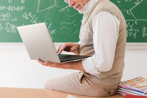 Älterer lehrer, der auf schreibtisch sitzt und auf laptop surft