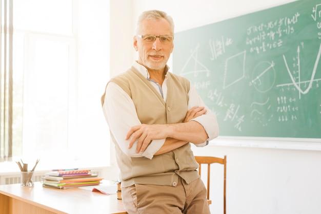 Älterer lehrer, der nahen schreibtisch im klassenzimmer steht